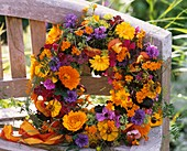 Autumnal wreath of helenium, phlox etc. on bench