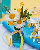 Posy of marguerites and buttercups in turquoise bottle