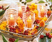 Roses, cherries and windlights on silver tray