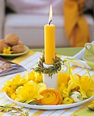 Candlestick with candle, willow wreath, narcissi, ranunculus