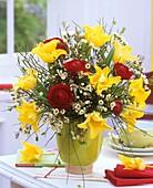 Arrangement of ranunculus, tulips, broom and wax flowers