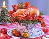 Arrangement of roses, Douglas fir, red winterberries & bauble
