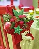 Red felt star with Douglas fir, apple, bauble on chair back