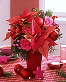 Arrangement of poinsettia, roses, ilex berries and baubles