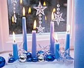 Blue candles, baubles and stars on tray by window
