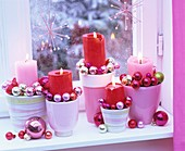 Adventliches Kerzengesteck mit kleinen Baumkugeln am Fenster