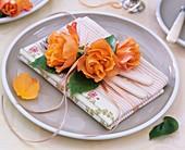 Napkin decoration of orange roses