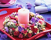 Flower wreath around pink candle on tray