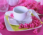 Place-setting with cup & saucer & fragrant hyacinth flowers