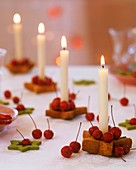 Star-shaped candle holders with crab apples & white candles