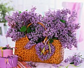 Lilac in plaited basket, gift boxes beside it