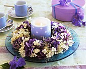 Wreath of hydrangeas and sea lavender around blue candle
