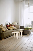 Sofa with cushions in period sitting room with wooden floorboards