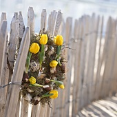 Easter wreath with yellow tulips on garden fence