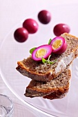 Quails' eggs marinated in beetroot juice on bread