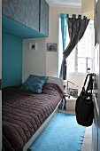 View into colour-coordinated bedroom with single bed below wall-mounted cupboards