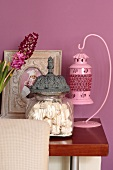 Pink lantern, glass jar of meringues and framed baby photo against lilac wall