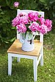Peonies in enamel pot on garden chair