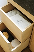 Open wooden drawers containing white towels and sea sponge