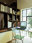 Simple workstation in front of loft window and partition shelving on low wall