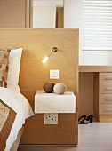 Headboard made of half-height partition with integrated reading lamp and bedside table