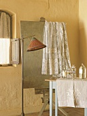 Romantic, vintage-style bathroom with lace curtain hanging over old easel and old apothecary jars