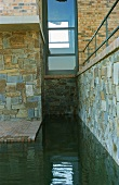 Pool surrounding stone-clad plinth of contemporary house