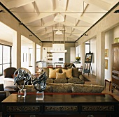 Open-plan, modern interior with colonnades on both sides and traditional furniture, some antique
