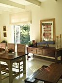 Dining room in rustic, country-house style with wall ornament on sideboard next to open French doors