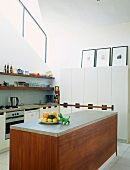 Modern, white fitted kitchen and island counter with stone top on wooden base unit