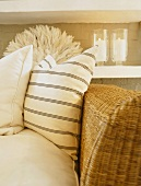Pale scatter cushions against backrest of wicker sofa