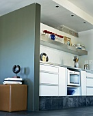 Simple, modern kitchen counter in niche and contemporary metal sculpture against grey partition wall