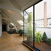 Offener Wohnraum im Dachgeschoss mit Schiebefenster zum Balkon und Nische mit Arbeitsplatz