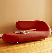 Rotes, gerundetes Designer-Sofa auf Rollen vor beigefarbener Wand