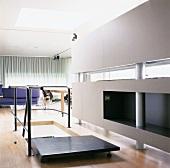 Mittig angeordneter Treppenaufgang mit umlaufendem Geländer im offenen Wohnraum