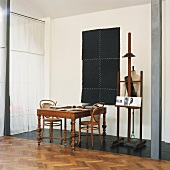 Antique wooden table, Thonet chairs, tailors' dummy and old easel in corner of loft apartment