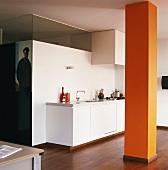 Open-plan interior with white kitchen counter and orange column