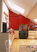Wohnküche im ausgebauten Dach mit roten Oberschränken und transparenten Acryl-Stühlen