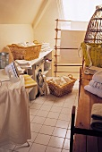 Attic laundry room with baskets of washing and an iron