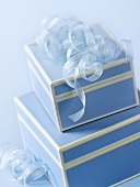 Two blue gift boxes with ribbons