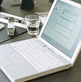 Aufgeklappter, weisser Laptop und Wasserglas auf einem Schreibtisch