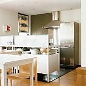 Offene Küche mit Edelstahl Elementen und Tresen mit Geschirrfach vor dem Esstisch
