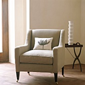 Armchair on dainty castors and stack of beakers on side table