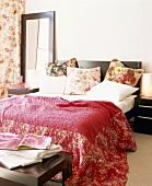 Schnörkellose Schlafzimmer-Einrichtung in dunklem Holz mit floral gemusterten Stoffen