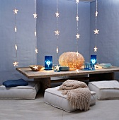 Rustic coffee table decorated with light art surrounded by floor cushions