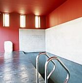 Klare, kräftige Farbgestaltung in einem Schwimmbad; Stahlrohrgeländer für Einstieg in schmales Wasserbecken