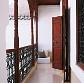 Erschliessungsbalkon mit Geländer und offenen Holztüren im orientalischen Stil