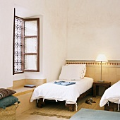 Simple, Oriental-style bedroom with half-height tiled wall and wrought iron window grille