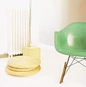 50er Jahre Sessel mit grünem Schalensitz und Fuss einer 70er Jahre Bogenlampe hinter geflochtenen Bodenkissen