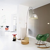 Offener Wohnraum im Loftstil mit grünem 50er Jahre Schaukelsessel, 70er Jahre Bogenlampe und Zwergen-Beistelltisch